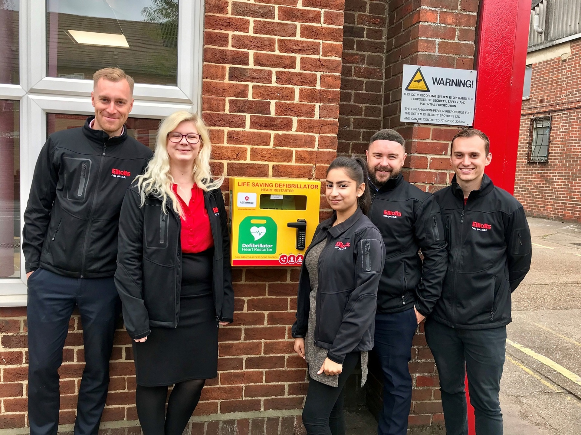 Elliotts employees with one of the new 24-hour access defibrillators