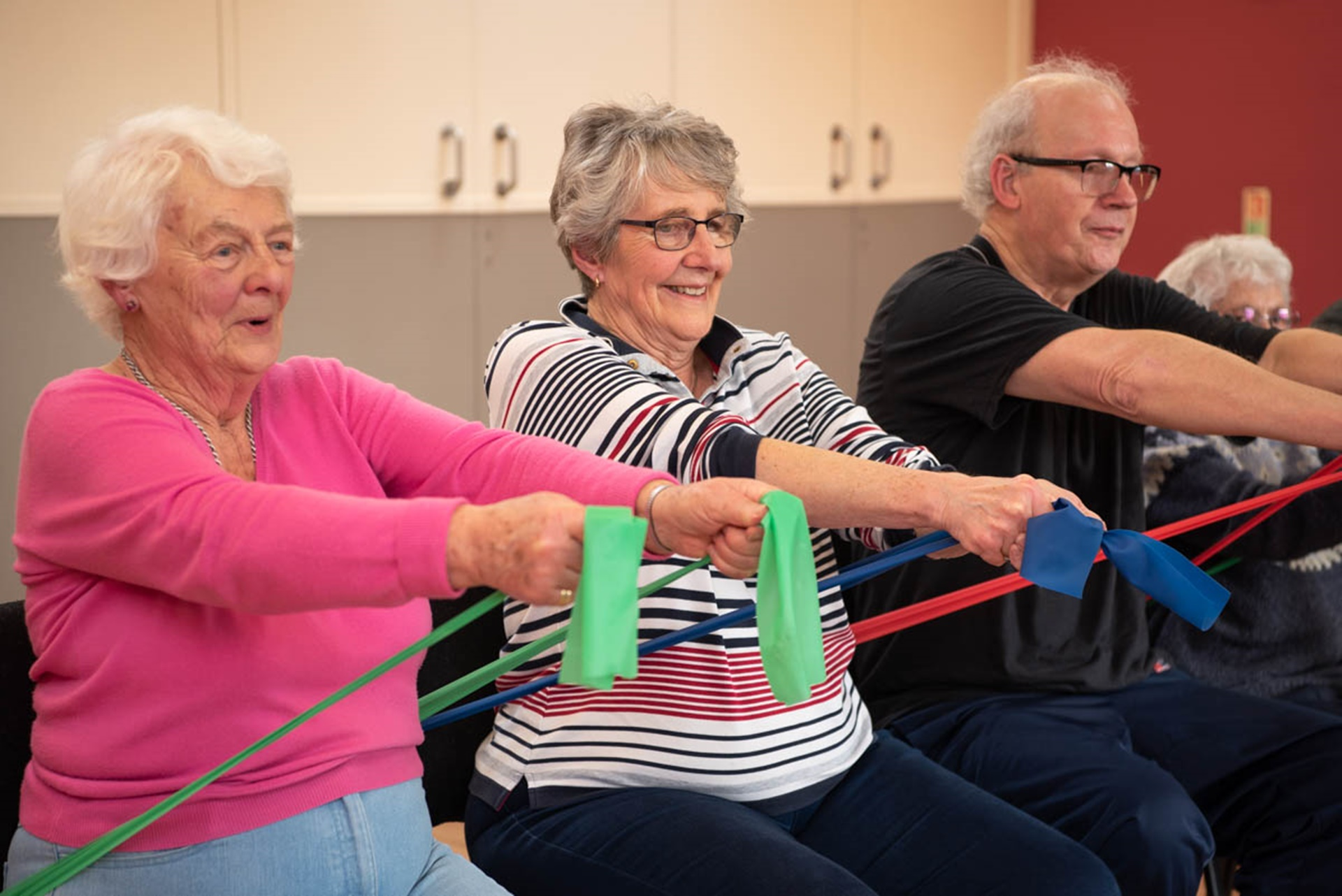 Seated chest press using theraband in group