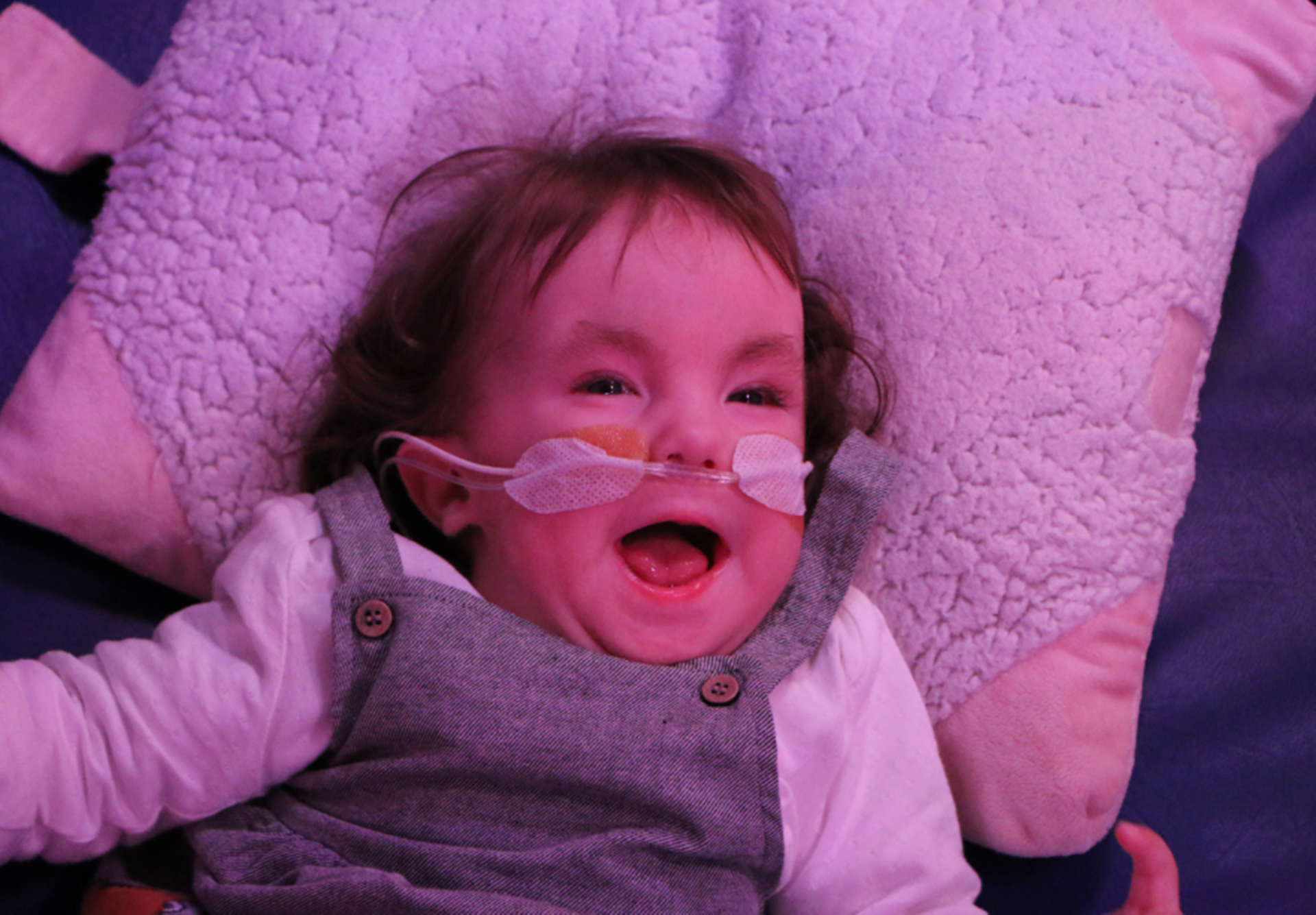 Little girl laughing in sensory room at Naomi House